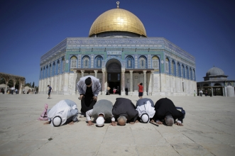 Muslim pray with backsides to Dome of the Rock