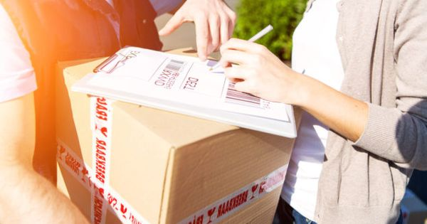 View of a Young attractive woman receiving parcel at home